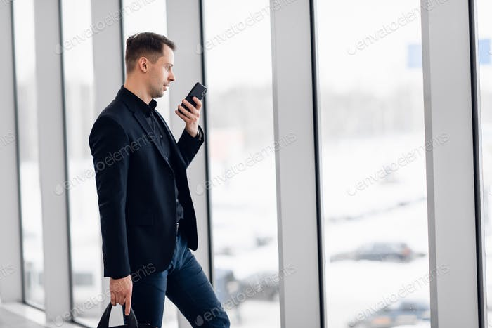 Concentrated businessman recording voice message at airport