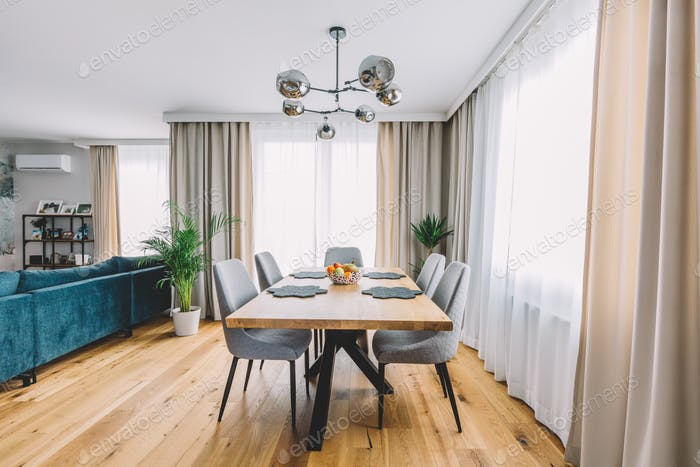 Dining room with wooden table and floor in modern apartment.