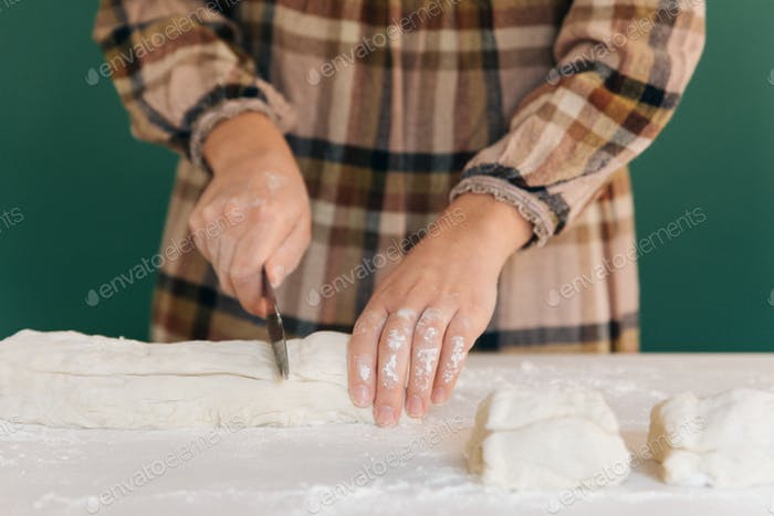 Woman cuts pieces of dough to prepare her handmade bread, homemade cooking.