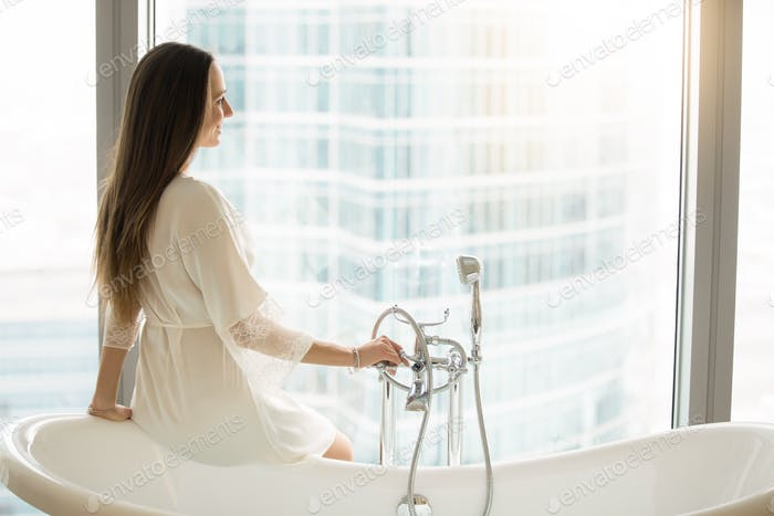Young woman near the tub