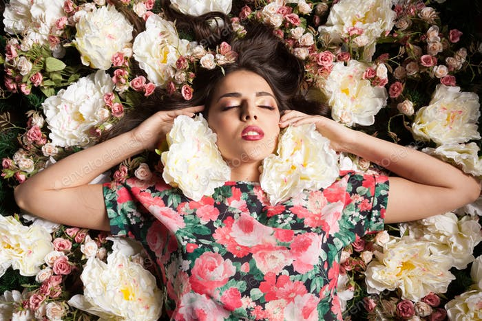 Sexy woman with eyes closed lying down on flowers