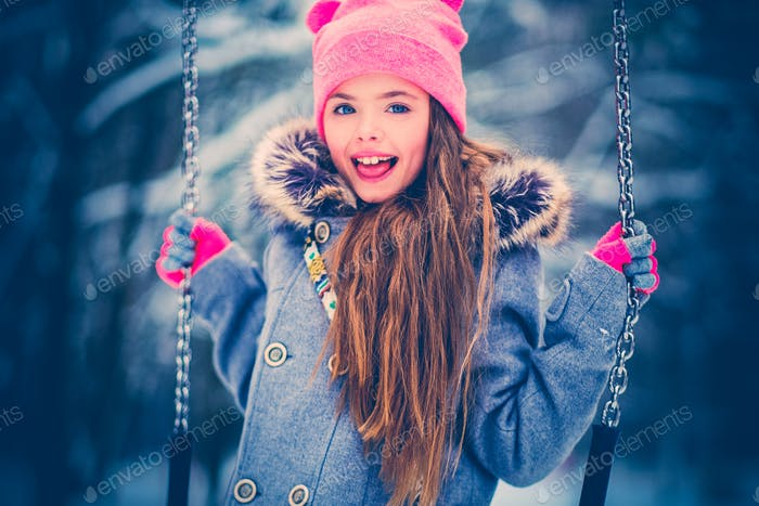 Charming little girl on swing in snowy winter