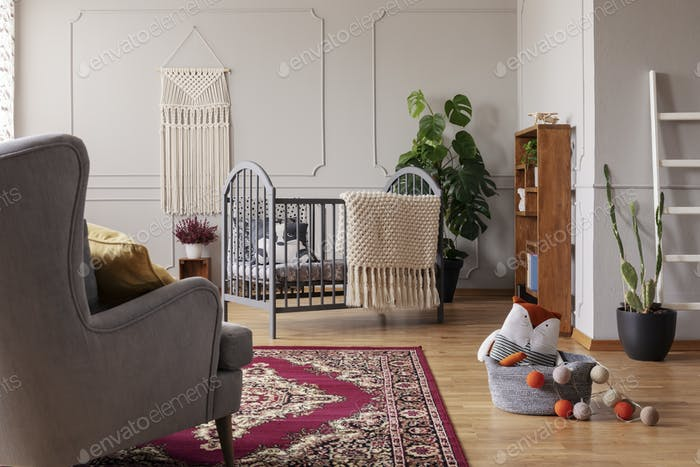 Grey and stylish baby room interior with wooden crib and handmade macrame on the empty wall