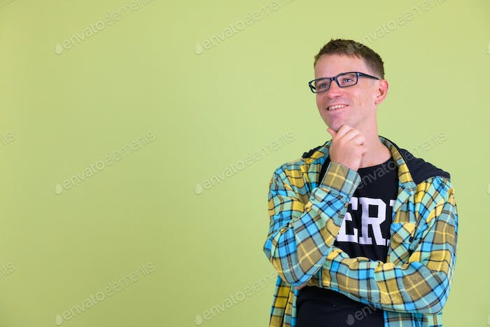 Portrait of happy nerd man with eyeglasses thinking and looking up