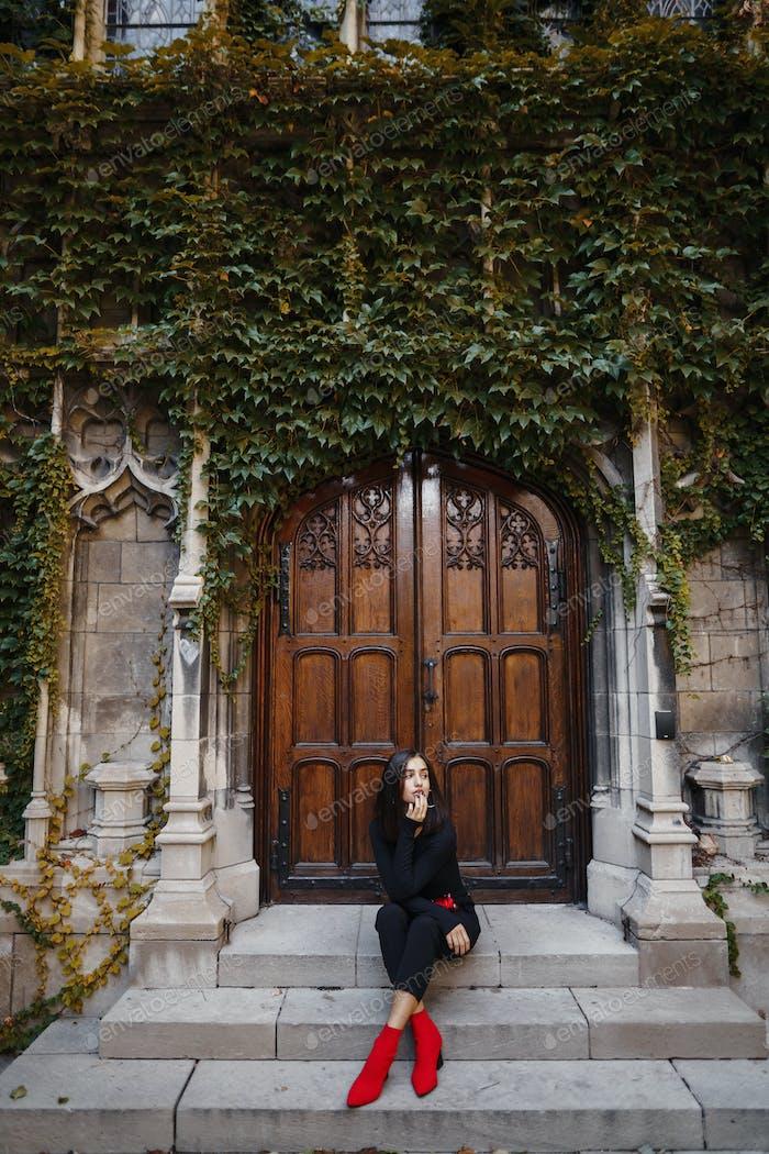 elegante morena chica sentado en el escaleras