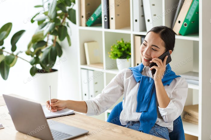Image of young asian woman talking on cellphone while working in office