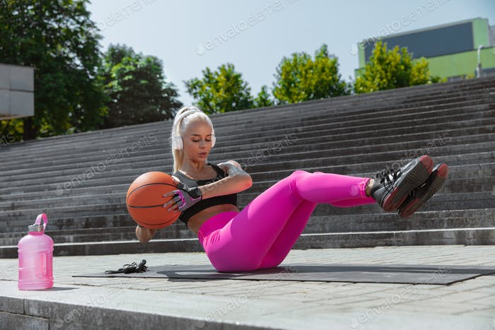 A young athletic woman working out at the city's street
