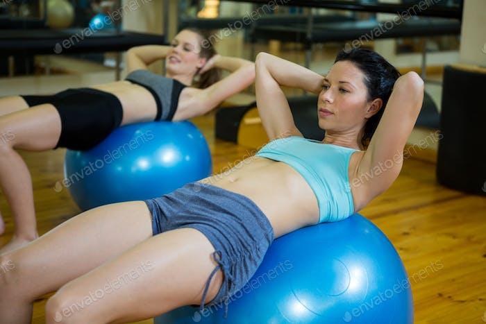 Determined women exercising on fitness ball