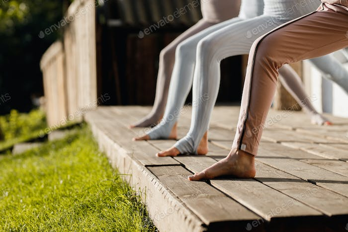 Four girls are practising yoga on a wooden podium in the garden in the open air