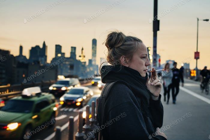 Frau steht auf der Brücke und raucht Zigarette, Stadtbild im Hintergrund