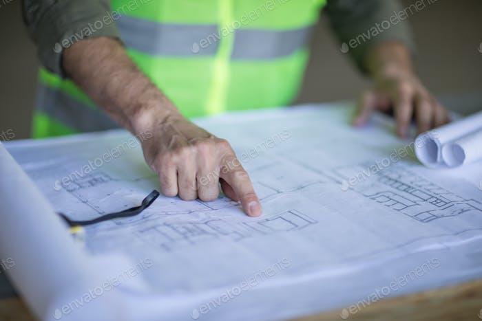 Zugeschnittene Aufnahme eines professionellen Ingenieurs, der Maßband hält und mit Blaupausen arbeitet