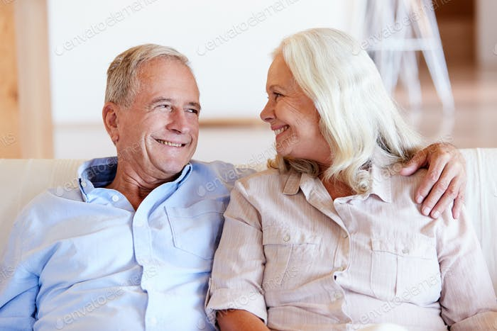 Senior white couple relaxing at home, looking at each other smiling, front view, close up