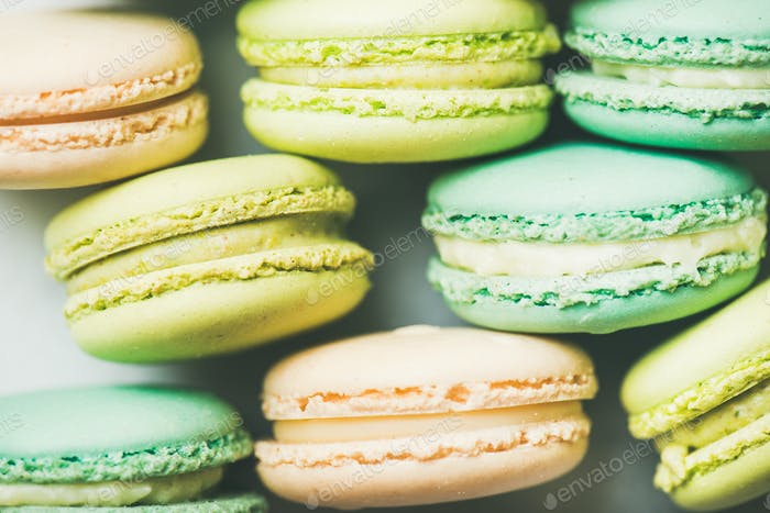 Pastel colored French macaroons cookies over light background