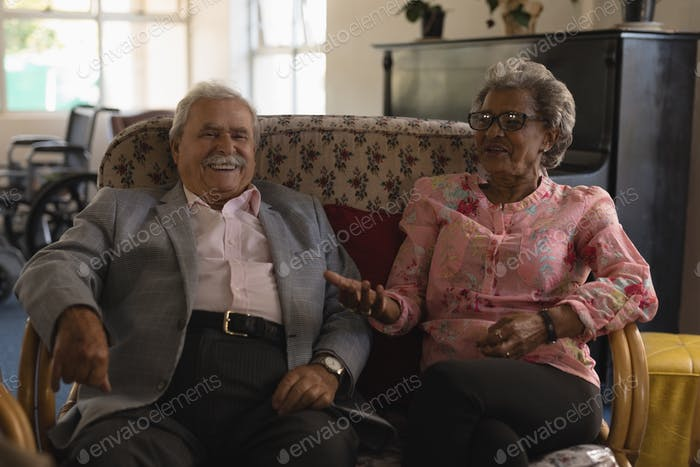 Front view of happy senior couple laughing and interacting with each other at home