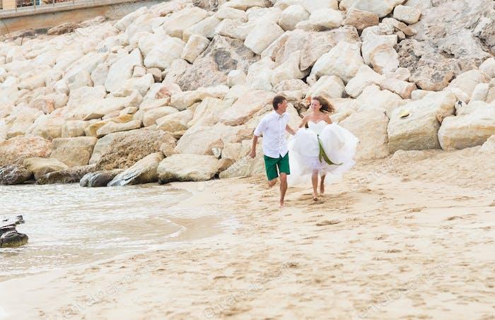 Glückliche gerade verheiratet junge Hochzeitspaar feiern und Spaß am schönen Strand haben