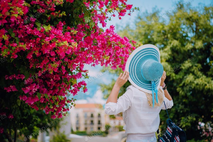 Elegant traveler woman with straw hat smelling beautiful colorful flowers on the islands of Greece