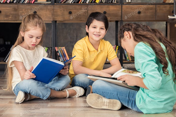 boy and girls reading books in library