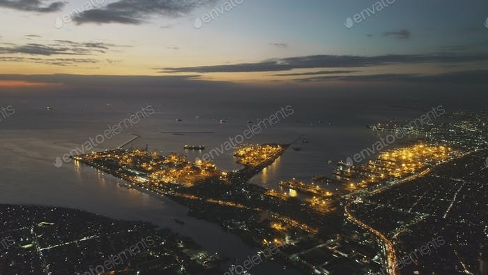 Illuminated cityscape at ocean bay aerial. Neon lights of town. Metropolis city roads, streets