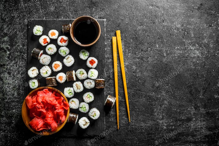 Sushi rolls on a stone Board with soy sauce and ginger.
