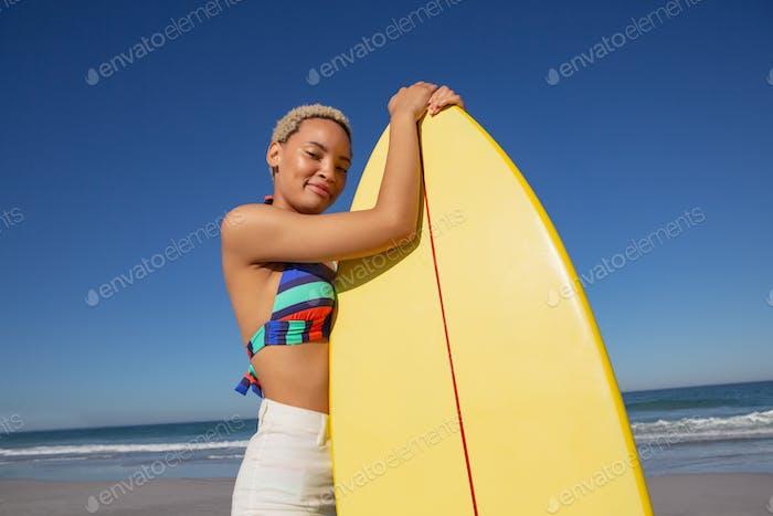 Schöne afrikanische Frau im Bikini stehend mit Surfbrett am Strand in der Sonne