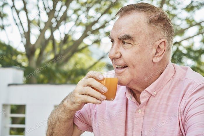 Happy aged man drinking juice