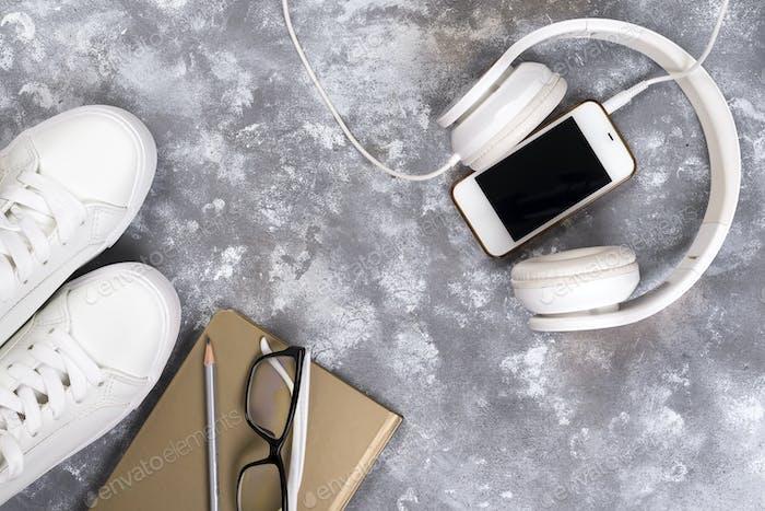 Sommerferien Konzept: Smartphone, weiße Turnschuhe, Notizblock, Kopfhörer, Stift