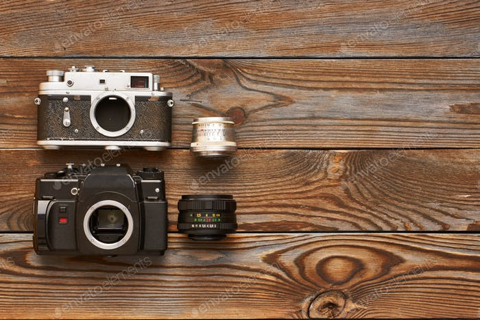 Vintage old cameras and lenses on wooden background