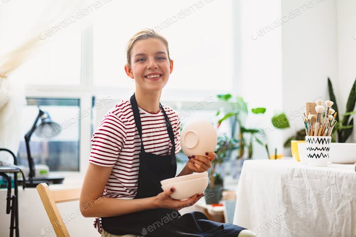 Pretty smiling girl in black apron and striped T-shirt holding handmade bowls in hands