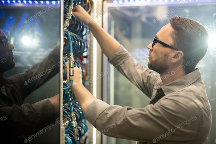 Data center engineer examining cables