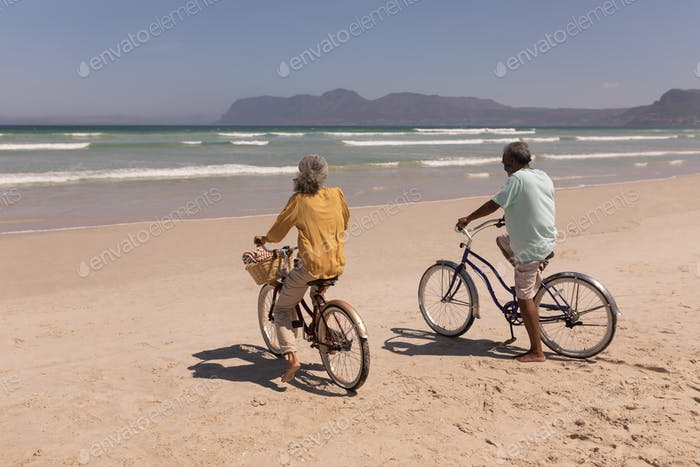 Senior couple with bicycle standing on beach in the sunshine with mountains in the background