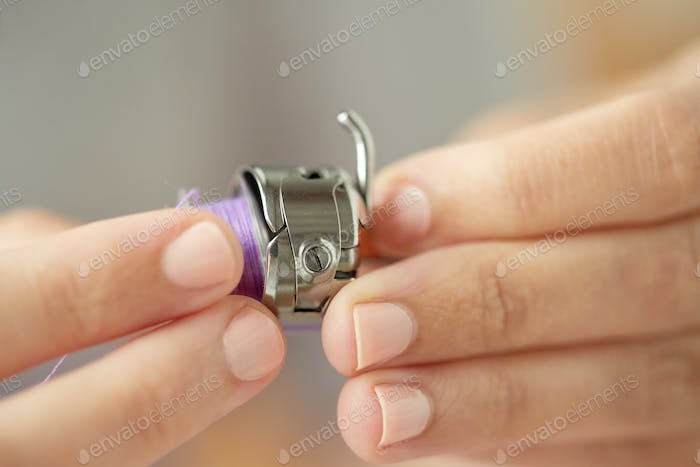 tailor hands with spool of sewing machine