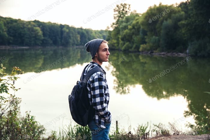 Young Man standing alone outdoor Travel Lifestyle concept with lake
