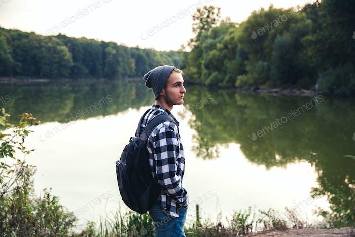 Young Man stehend allein Outdoor Travel Lifestyle Konzept mit See