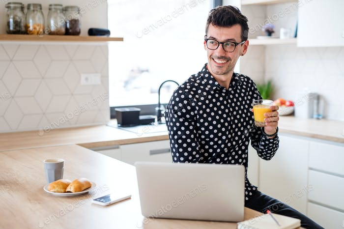 Young man with laptop sitting in kitchen, a home office concept
