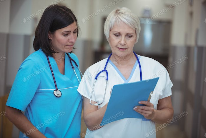 Female surgeon and nurse having discussion over file in corridor