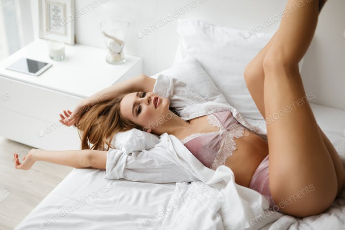 Young beautiful lady in lingerie and white shirt thoughtfully looking in camera while lying in bed
