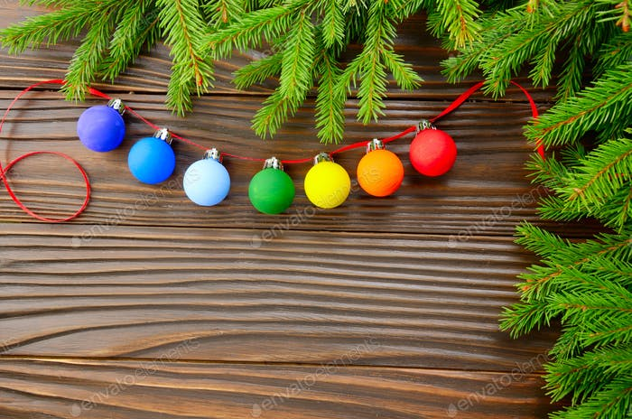 Christmas background of spruce branches and colorful balls on wooden table