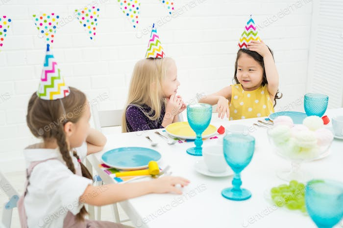 Cute multi-ethnic girls chatting at birthday party