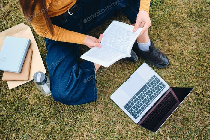 Close up casual student girl studying with laptop and book on lawn in park