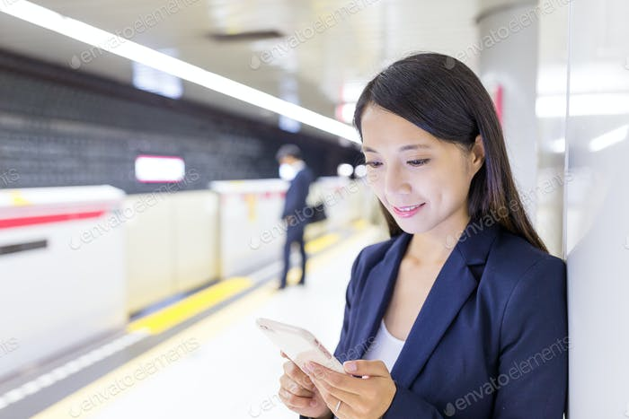 Businesswoman working on cellphone in train platform