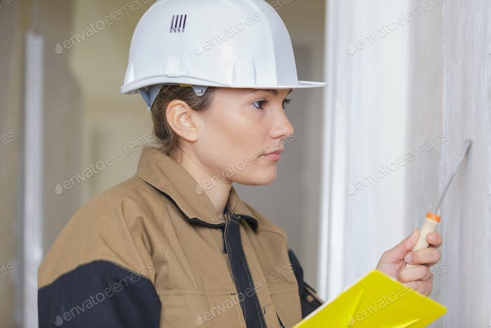 female holding a screwdriver in a site
