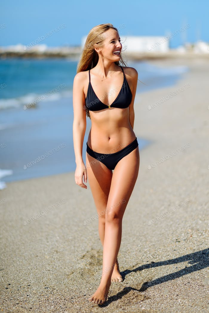 Young blonde woman with beautiful body in swimwear on a tropical beach.