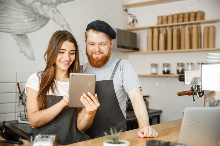 Coffee Business Concept - Satisfied and smile owners couple look on tablet orders online in modern