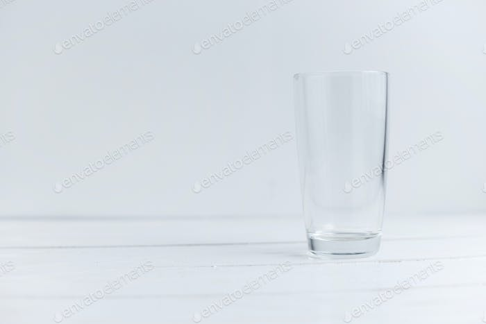 Close up view of empty glass standing on white wooden table