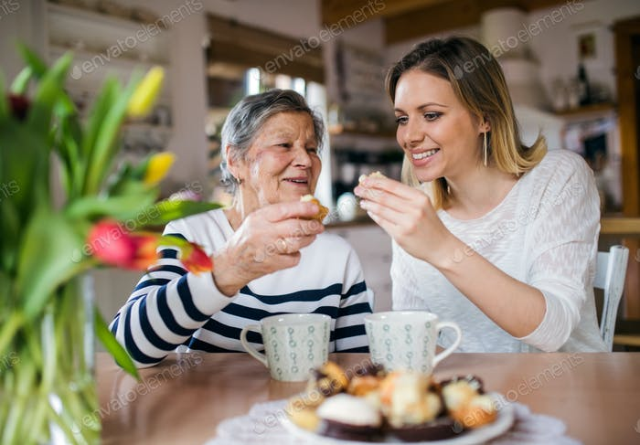 An elderly grandmother with an adult granddaughter sitting at the table at home, eating cakes.