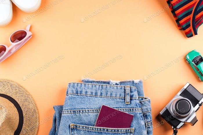 Travel items flat lay on orange with camera