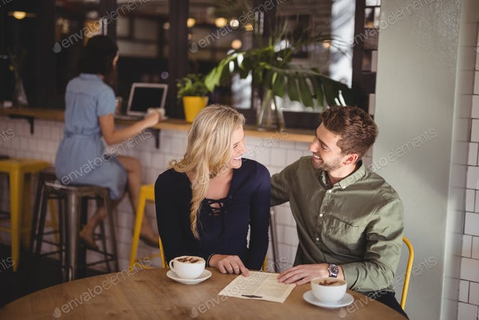 Happy couple talking while sitting with coffee cups and menu at table