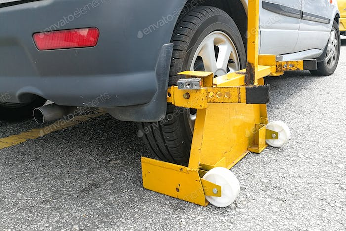 Car wheel clamp on street for illegal parking