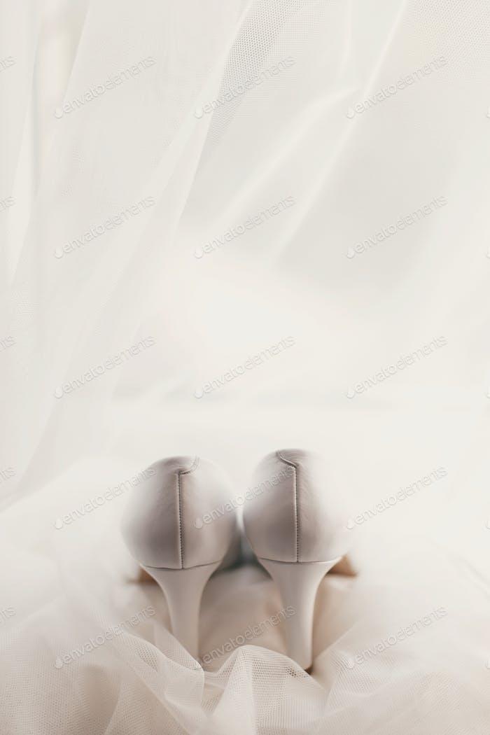 Beautiful stylish shoes on luxury silk wedding dress