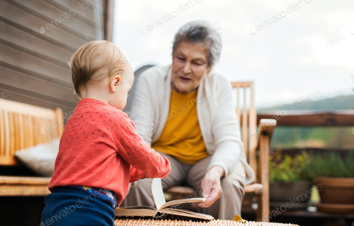 Elderly woman with a toddler great-grandchild on a terrace in autumn.